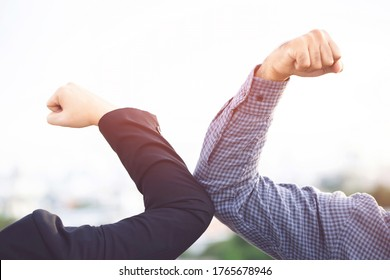 Two people Elbow bump. New normal novel greeting to avoid the spread of corona virus. business man meet with bare hands social distancing. no hug or handshake. Stop outbreak.