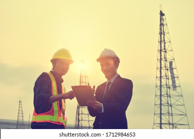 Two people Engineer use tablet device standing communication at construction building background on morning