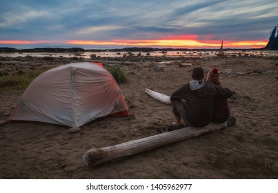 Two people enjoying a sunset at a campsite after a long day hiking the West Coast Trail on Vancouver Island, British Columbia, Canada.