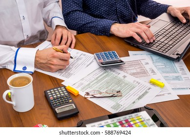 two people filling tax forms, helping each other.