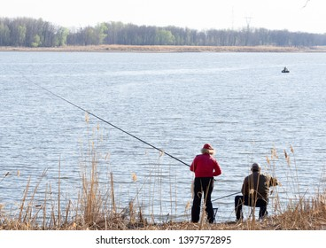 Two people are fishing on the river bank.