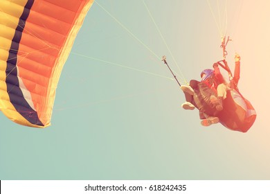 Two people are flying on a paraglider in the sky. Toned