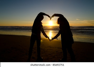 Two people forming a heart with their hands during a sunset