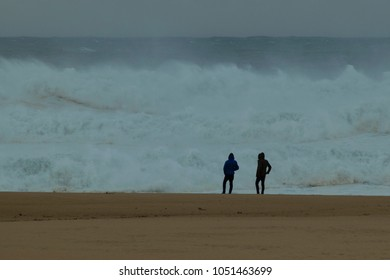 Two people in front of a huge wave on the Praia do Norte beach in Nazare, Portugal.