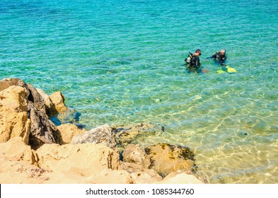 Two people with full equipment dive in turquoise water near the rocky coast