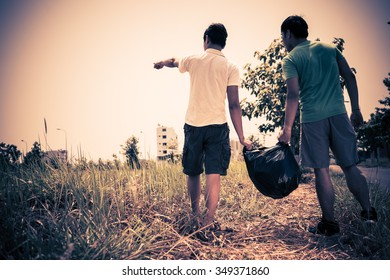 Two people with full garbage bag looking in distance