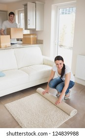 Two people furnishing the house while holding boxes and rolling out a carpet