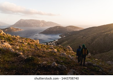 Two people and goats hiking down a mountain during sunset in Kalymnos Greece.