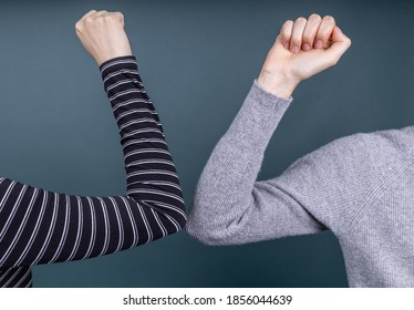 two people greeting each other with elbows