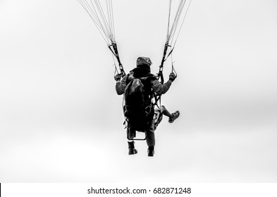 Two people hang gliding together; teamwork concept, trust concept, black and white image