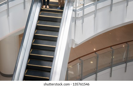 Two people heading down the escalator to go the lower floor