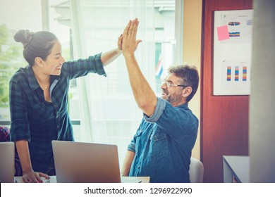 Two people hi five together for thier successful business project in meeting room. Two of business people looking at each other