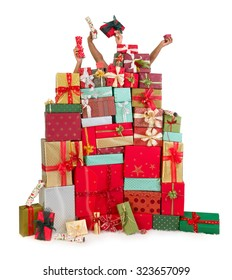 Two people hiding behind a huge stack of christmas presents