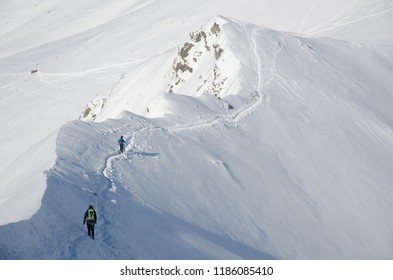 Two  people hiking in Polish Western Tatra mountains during sunny day in winter.