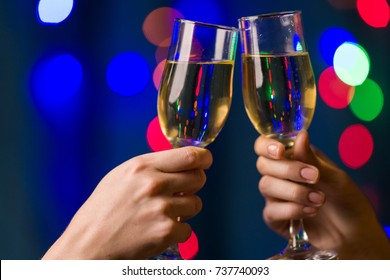 two people holding glasses with champagne on a blurred background of multicolored twinkling Christmas lights, closeup