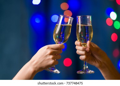 Two people holding glasses with champagne on a multicolored blurred background of Christmas lights