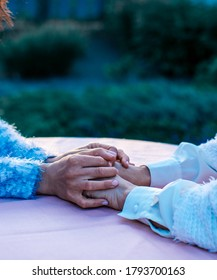 Two people holding hand together over blurred nature background. Hands concept. Photo.