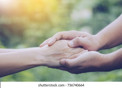 Two people holding hand together over blurred nature background,Business man and woman shaking hands,helping hand  and world peace concept with copy space