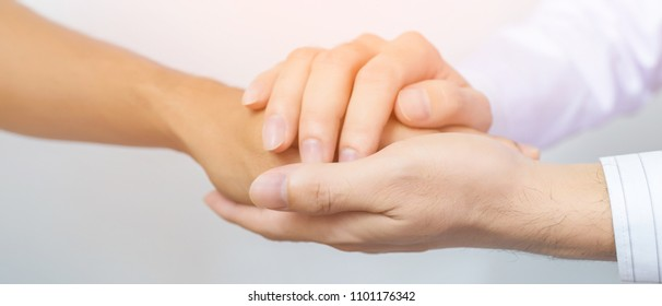 Two people holding hands for comfort. Doctor consoling relatives of patients in hospital concept banner panoramic crop for copy space.