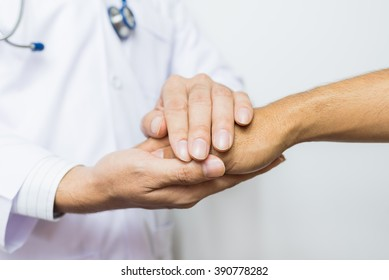 Two people holding hands for comfort. Doctor Joins Patients. Doctors wear white.