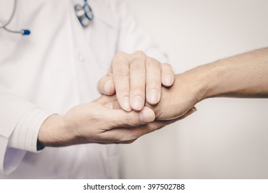 Two people holding hands for comfort. Doctor consoling relatives of patients.  Vintage tone.
