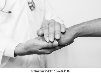 Two people holding hands for comfort , black and white.