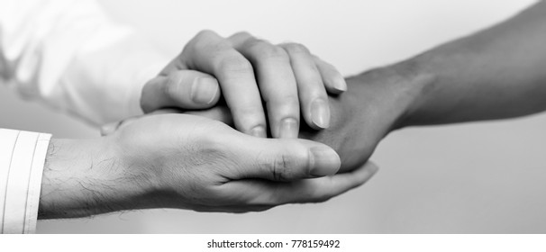 Two people holding hands for comfort. Doctor consoling relatives of patients in hospital concept. black and white. banner panoramic crop for copy space.