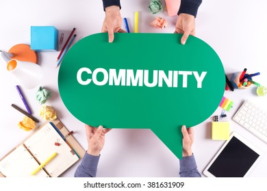 Two people holding speech bubble with COMMUNITY concept