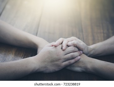 two  people join hands and  praying together on wooden table with the light from above with copy space fro your text.