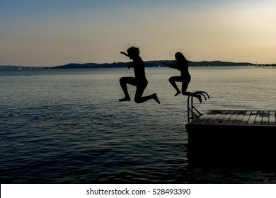 Two people jumping into the lake
