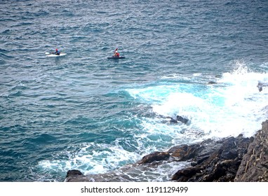 two people in kayak paddle on the stormy sea with breaking waves along the rocky coast