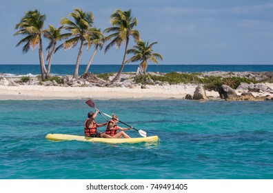Two people kayaking in the Caribbean sea. Young happy couple traveling on a row boat. Recreational activities on the water.