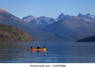 Two people kayaking on the mountain lake