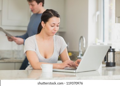 Two people are in the kitchen and reading a magazine and working on the laptop