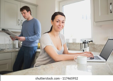 Two people in the kitchen using the laptop and reading a magazine