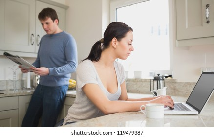 Two people in the kitchen who are using the laptop and reading a magazine