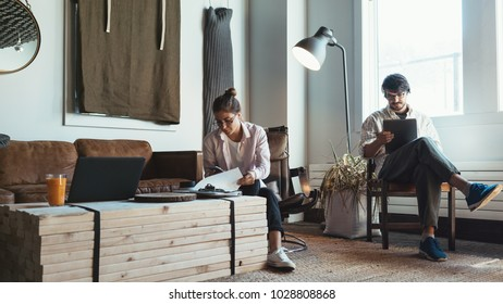 Two people with laptops in small loft office. Man and woman working together
