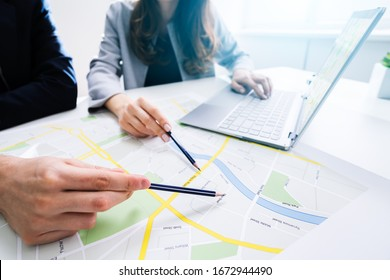 Two People Looking At City Map With Laptop At Table
