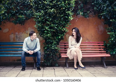 Two people looking at each other sitting on different benches.