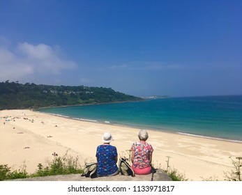 Two people looking at the view in Carbis Bay beach on a sunny day with blue skies and blue sea near St Ives Cornwall June 2018