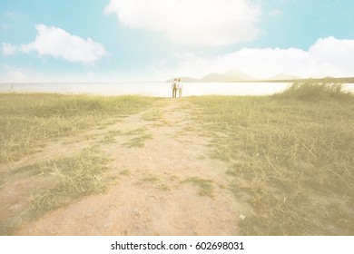 Two people as lovers standing in meadow landscape with blue sky as vintage tone