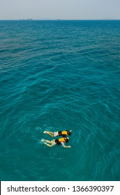 Two people man and woman catch each other hands and happy with nature and skin diving to see reefs and bottom of sea in clear water.