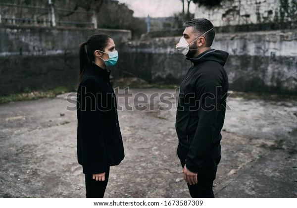 Two people in masks talking from distance.Couple being divided by incurable infectious disease.Infection control,isolation.Loved one illness.Saying goodbye.Farewell.Toxic relationship.