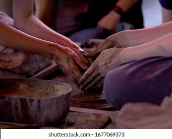 Two people molding clay on a wheel