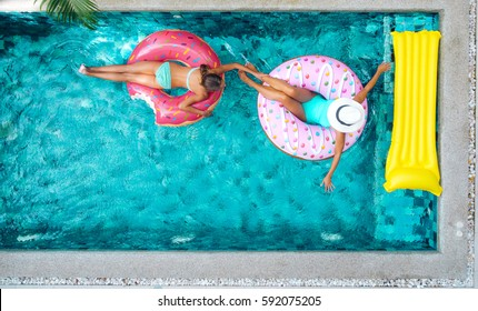 Two people (mom and child) relaxing on donut lilo in the pool at private villa. Inflatable ring and mattress. Summer holiday idyllic. High view from above.