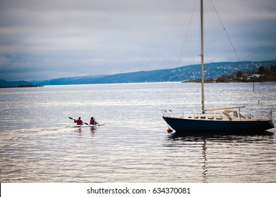 Two people on a kayak are sailing past the yacht. Oslo, Norway