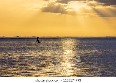 Two people on a paddle board moving towards the sunset. This photograph was taken at the Trou d'eau, a beach in the commune of Saline les bains on Reunion Island in the Indian Ocean.
