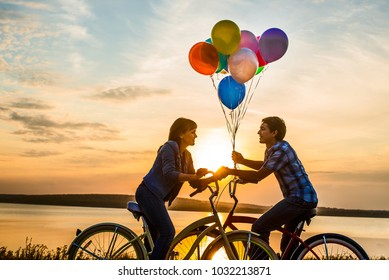 two people on romantic date looking each other. Young couple sitting at one bicycle.Girl holding colorful balloons on sunset cloudy sky background. man and woman. boy and girl on romantic date
