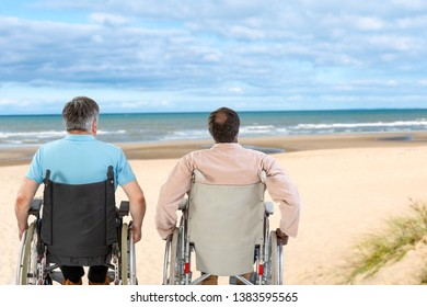 Two people on wheelchairs with mobility problems on the sea beach,looking away