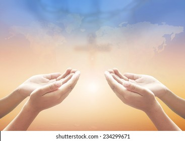 Two people open empty hands with palms up, over blurred cross with world map of clouds on sunset background